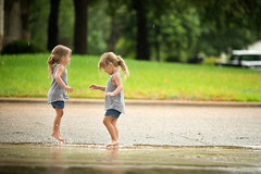 Enjoying the Rain (donnierayjones) Tags: twins girls children child girl twin sister sisters road rain texas water play dance dancing green grass trees neighborhood street driveway ponytail shorts toddler toddlers 3yo raining