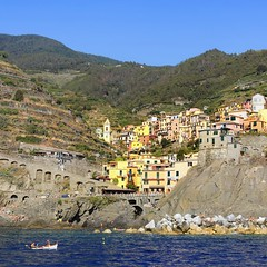 Manarola suspended between sea and land on sheer cliffs (Bn) Tags: above travel blue sea summer sky italy house holiday nature water colors yellow architecture swimming coast harbor boat cool intense fishing topf50 rocks colorful mediterranean italia day village fishermen terrace walk liguria dramatic calm cliffs lovers unesco via adventure clear caves vineyards terre cape waters coastline summertime cinqueterre elevated soaring manarola hamlet thrill cinque steep jewel italianriviera dellamore ligurian 50faves unspoiledshores