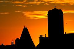 See the sun rising over The Hague (-Aus-) Tags: city november blue sky urban orange sun tower church silhouette clouds sunrise rooftops dusk hague roofs