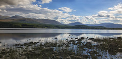 by the bonnie banks of Loch Morlich (lunaryuna) Tags: scotland cairngorms northerncairngorms nationalpark landscape lake lochmorlich shoreline mounrains sky clouds cloudscape weather latesummer season seasonalbeauty water rocks grasses le longexposure panoramicviews lunaryuna