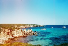 Cala Pudenta (ianjmorton) Tags: menorca spain balearic island sea sky boat lightleak olympus trip