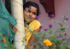Day Dreaming Along the Canal (The Spirit of the World) Tags: girl child local flowers posing kerala india southernindia house portrait candid