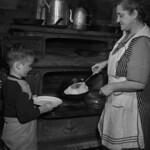 Child and mother cooking pancakes on two bridge stove - sugar bush camp / Un enfant et sa mère font cuire des crêpes dans un four à deux étages d'une érablière thumbnail