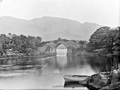 On the bridge below the mountain! (National Library of Ireland on The Commons) Tags: robertfrench williamlawrence lawrencecollection lawrencephotographicstudio thelawrencephotographcollection glassnegative nationallibraryofireland bridge lake mountain mailcoach boat scene timing killarney countykerry brickeenbridge muckross lakesofkillarney muckrossdemesne demesne arch locationidentified coach