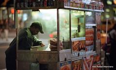 Street food (Rafakoy) Tags: city nyc light people urban food ny newyork color colors night work lights manhattan candid grain working negative timessquare streetfood highiso 105mm nikonf6 c41 kodakektar1000 epsonv600 epsonperfectionv600 afnikkor105mmf2ddc