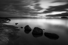 Along the shore (- David Olsson -) Tags: longexposure sunset blackandwhite bw lake seascape nature water monochrome clouds landscape mono nikon october rocks sundown cloudy sweden dusk stones tripod shoreline cliffs karlstad le grayscale fx vnern 2012 linedup vrmland 1635 ndfilter d600 1635mm lakescape smoothwater skutberget smoothsky davidolsson nd500 lightcraftworkshop 1635vr