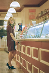 Sweets (e.m.alder) Tags: 105mmf25p 135 35mm c41 canoscan9000f ftn kodak nikkor nikkorp105mmf25 nikon nikonf photomic portra portra400 analog film homedevelopment indoor candid portrait people woman girl female model beauty fashion dress warm grain icecream candy shop huntsville ontario canada store cafe coffee espresso