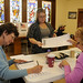 Ashley Dupuis takes her ballot from election inspector Mae LaMare while Elaine Lemieux finishes getting her signed in at the Adirondack Adult Center in Tupper Lake. Photo: Mark Kurtz
