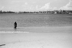 Adventures' beginning (Albion Harrison-Naish) Tags: blackandwhite woman film beach water monochrome analog landscape grey nationalpark small grain sydney australia calm nsw newsouthwales serene anticipation contemplative ilforddelta400 potential sydneyharbour minoltadynax7000