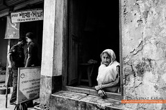 A portrait in time (Neerod [ www.colorandlightphotography.com ]) Tags: door old woman wall lady tooth time police age wait crumble widow bangladesh bnw sindur shakha