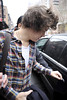 Harry Styles of One Direction is surrounded by fans and photographers as he leaves his hotel in New York City