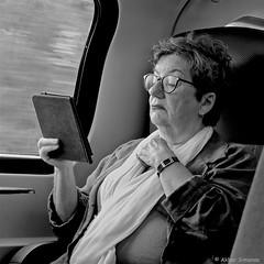 E-READER (Akbar Simonse) Tags: dscn3020 trein train passenger traveller reiziger holland netherlands nederland people candid woman vrouw streetphotography straatfotografie vierkant square zwartwit bw blancoynegro bn monochrome akbarsimonse glasses bril ereader watch horloge