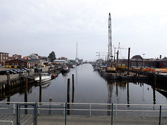 The canal in Cuxhaven in the morning (Notquiteahuman1) Tags: canal cuxhaven boats saltwater northsea morning blue street cars cranes water transportation handheld compactcamera bridgecamera germany catwalk mar mardonorte barcos reflection