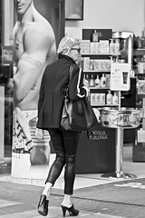 Mutton dressed as lamb... (NRG Photos) Tags: old blackandwhite woman feet sunglasses fashion poster shoes legs alt candid frau mode handbag schuhe plakat sonnenbrille beine fountainofyouth jungbrunnen handtasche muttondressedaslamb perfumery schwarzweis parfmerie schnappschus fse aufjungmachen
