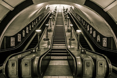 Stepping Back in Time (Daniel Borg) Tags: camera city light england blackandwhite bw white black london lines sepia architecture stairs buildings underground lights unitedkingdom pov escalator tube wideangle tunnel stairwell tubestation londonunderground canon1022 hintofcolour danielborg humanelement londontrainstation canon550d cityandarchitecture
