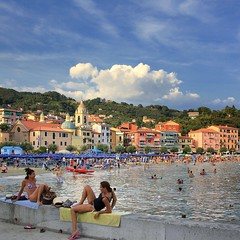 Relaxing afternoon in the multi-colored Ligurian town of San Terenzo (Bn) Tags: pink blue trees houses girls sunset sea summer vacation sky italy panorama orange dog holiday seascape green castle beach water colors beauty yellow pine clouds swimming walking bay coast la oak sand ancient topf50 women san italia hiking turquoise magic liguria charm tourist panoramic medieval historic hills bikini vista colored lush viewpoint colori multi parasols lerici swimmng spezia ligurian liguri 50faves terenzo towerhouses panview golfdeipoeti