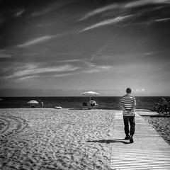 Walk by the sea (jfraile (OFF/ON slowly)) Tags: playa cielo nubes mar arena sombrilla pasarela blancoynegro barcelona platjadelamarbella streetphotography jfraile javierfraile sky clouds sea beach sand