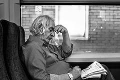 Puzzled (EyeOfTheLika) Tags: ifttt 500px monochrome portrait man one street sit people chair window elderly book newspaper lika lomdon london transport train photographer
