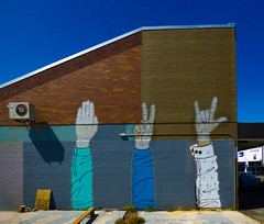 Evolution (Steve Taylor (Photography)) Tags: art graffiti mural streetart building blue brown white brick bench newzealand nz southisland canterbury christchurch sunny sunshine shadow salute nazi peace iloveyou arm hand sleeve ac unit airconditioner plank
