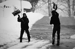 shovel wars (Barbara.K) Tags: winter people blackandwhite snow playing candid snowstorm monochromatic streetphoto bloomingtonin eos500d canonefs55250mm canonrebelt1i