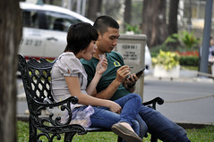 Food and thought (Roving I) Tags: friends sitting technology eating wroughtiron parks couples vietnam snacks mobilephones saigon hochiminhcity communications hcmc cellphones smartphones communicating