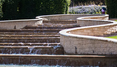 Not just for rainy days... (Suzanne.Russell) Tags: alnwickcastlegardens fountain softplanting solitaryfigurewithumbrella sunshine summer curves stonewalls water