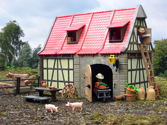 Busy at the barn (PeterDB.net) Tags: photo toy toys playmobil klicky steck vintage old medieval farm barn stable truss wall fachwerkhaus cow pig piglet wheelbarrow outdoor roof sky joby gorillapod halftimbered