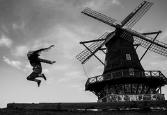 Soaring in Sweden (Ted Somerville) Tags: windows sky bw woman white motion black windmill girl beauty stone countryside fly flying blackwhite wings movement pretty wind action sweden air country flight free floating molino janela sverige soaring malmo voar voo voando hangtime nyhamn molion janeis