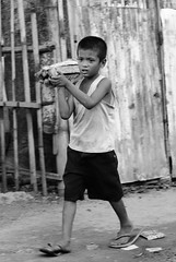 Life goes on (ubo_pakes) Tags: poverty road street wood city boy portrait bw work fence walking photography photo blackwhite kid nikon asia child body path labor philippines poor working dirt short cebu firewood slippers visayas carrying d60 ubo pakes inayawan mygearandme inayawanriversidedistribution