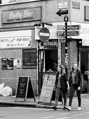 Northern Quarter #125 (Peter.Bartlett) Tags: manchester women window unitedkingdom city urbanarte peterbartlett shutter girl monochrome uk m43 couple bw noiretblanc fastfood people streetphotography doorway litter woman walking niksilverefex urban trash rubbish olympuspenf poster microfourthirds text corner lunaphoto sign blackandwhite candid cafe