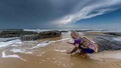 Crab Hunting (rameshsar) Tags: 8mm kovalam surfing rokinon xe2 child play clpuds rocks beach sand india