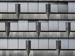 Facade adorned with short Pencils (Batikart) Tags: city windows light urban white house abstract black building art glass lines june wall juni architecture modern triangles f