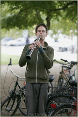 a clarinetist (PIKTORIO) Tags: berlin germany muaician streetmusician busker clarinet summer green tree bicycles piktorio performer musician