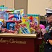 Retired U.S. Marine Corps officer helps load toys into grape gondola sleigh