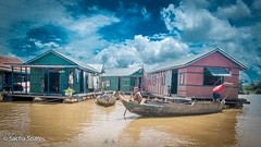 Boy from a Fishing Village (sachasplasher) Tags: oy boat village poor poverty cambodia asia fishing lake clouds sky house floating
