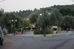 (Psinthos.Net) Tags:  psinthos psinthossquare square       cars road august    greenery pots flowers mountain shrubs sky    summer morning          pinetrees olivetrees trees treebranches   mulberry  leaves stonewall   mantel paved    pavement sidewalk nightlights    cable planetree   houses geranium      whiteblossoms pinkblossoms