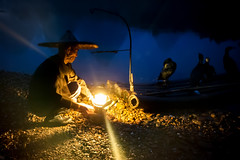 The Fisherman and The Lamp (TheFella) Tags: china lighting morning travel blue light portrait man mountains reflection slr water lamp hat birds night digital sunrise canon river cormorants person eos dawn liriver li boat photo fishing fisherman asia guilin candid fineart working chinese beam nighttime photograph figure processing limestone lone 5d mystical worker cormorant rays bluehour burst dslr beams lijiang starburst southchina mkii guangxi markii postprocessing travelphotography ricehat lijiangriver cormorantfisherman cooliehat thefella paddyhat 5dmarkii conormacneill thefellaphotography