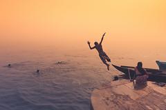 Diving. Varanasi, India (Marji Lang Photography) Tags: banaras benares bhärat bhäratgaá¹aräjya bã©narã¨s canoneos5dmarkii ef247028l ganga ganges gaudolia godaulia gowdolia hindu india indian indiansubcontinent kashi marjilang republicofindia travelanddocumentaryphotography travelphotography uttarpradesh varanasi ambiance ambience atmosphere atmospheric boat boats childhood children color composition diving documentary flood fog foggy fun gameoftones ghats holycity horizontal jump jumping kid kids light memories misty mood moody mysterious oldvaranasi oldcity oldtown pastel pilgrims river roamingboat scene sepia severalpeople severalpersons spirit spiritual tones travel warm water