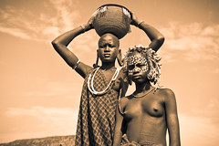 Mursi young women in the Mago national park. Ethiopia (NeSlaB .) Tags: poverty africa travel decorations portrait blackandwhite woman black girl beauty look hat sepia canon painting photo blackwhite necklace eyes women paint body traditional country culture photojournalism tribal clothes ornaments tradition ethiopia tribe ethnic society mago scar mursi scarification developingcountries reportage nationalgeographic coiffure afrique ethnography ethnology omo etiopia debub ethnies snnpr murzu neslab davidecomelli