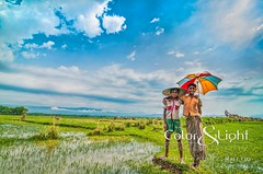 Colorful childhood (Neerod [ www.colorandlightphotography.com ]) Tags: blue sky cloud sun color green field youth rural umbrella children child shepherd sunny hills sylhet bangladesh
