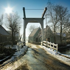 The characteristic wooden drawbridge in Zuiderwoude (Bn) Tags: wood bridge winter light sun white lake snow cold holland ice church water netherlands dutch sunshine amsterdam century wooden dorpsstraat topf50 day tour village bright farm skating nederland biking drawbridge rays 16th picturesque kerk oldest ae noordholland waterland houten witte noord boerderij situated ophaalbrug 50faves characteristic zuiderwoude hoiiday idyllically aandammergouw zuiderwouder