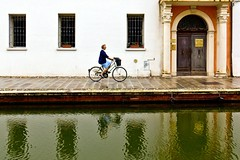 Comacchio, Italy (Kathy~) Tags: italy comacchio city life urban canals water buildings person people bike bikingalongthecanal reflection favescontestwinner thepinnaclehof tphofweek185 favescontestfavored herowinner ultraherowinner instagram