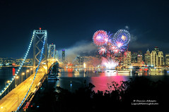 New Year's Eve Fireworks - San Francisco Style (Darvin Atkeson) Tags: sanfrancisco california city eve travel blue red white holiday reflection skyline season island bay cityscape treasure suspension fireworks location goldengate baybridge newyears yerbabuena 2012 2013