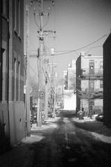 Alley (josephcarlson1) Tags: street city urban bw white snow black building tower cars wet glass minnesota metal digital skyscraper photoshop canon grit eos rebel holga blurry alley day no grain minneapolis sunny dirty pinhole blocks grime dslr vignette mn minn t2i