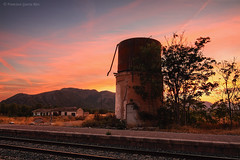 Puesta de sol en la vieja estacin./ Sunset at the old Railway Station. (Recesvintus) Tags: agramn helln albacete spain espaa railway ferrocarril station estacin vas rails rales puestadesol sunset evening twilight sundown dusk sky colors cielo depsitodeagua watertank recesvintus