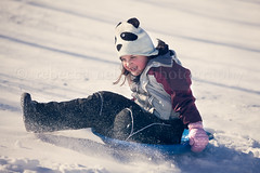 (Rebecca812) Tags: winter portrait snow girl hat childhood fun outdoors kid play action coat knit powder downhill cheerful excitement sled playful onthemove mittens stopmotion pandabear tobaggon snowhat reallifemoment animalrepresentation