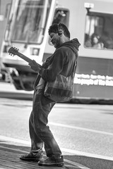 Launching Into The Strato-Sphere (Ian Sane) Tags: ian sane images launchingintothestratosphere man guitar stratocaster max train mass transit black white candid street photography southwest broadway downtown portland oregon canon eos 7d camera ef70200mm f28l is usm lens