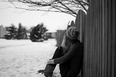 Winter's Chill (Samantha Stock) Tags: winter blackandwhite snow tree girl monochrome hat self fence sweater bokeh sony 365 366 nex5