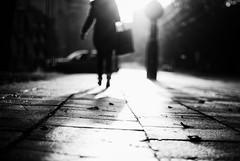 light shopping (ewitsoe) Tags: street city light blackandwhite bw woman shop lady contrast 35mm walking concrete 50mm nikon europe poland polska sidewalk purse purpose tilted poznan d80