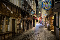 Main Street at Mont St Michel (adrianchandler.com) Tags: france normandy cobblestones street city montsaintmichel town buildings exterior nightscape night road avenue french creperie cafe rue architecture medievel late coast shops outdoor